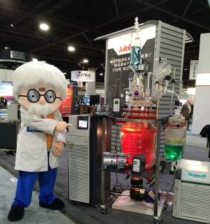 PITTCON mascot, Pete Con, standing beside the Julabo reactor